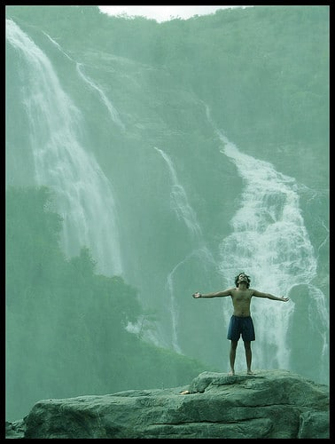 man with arms open at waterfall