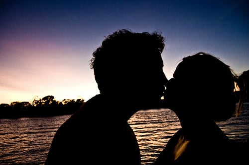 kissing behind a sunset