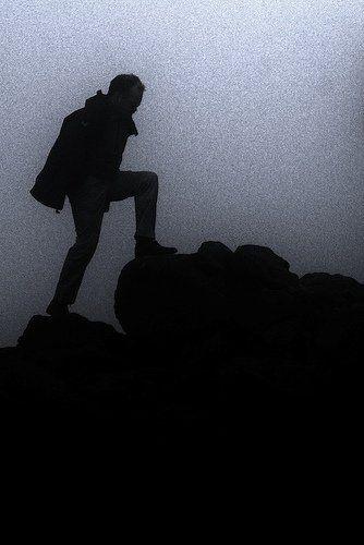 profile of man climbing a mountain