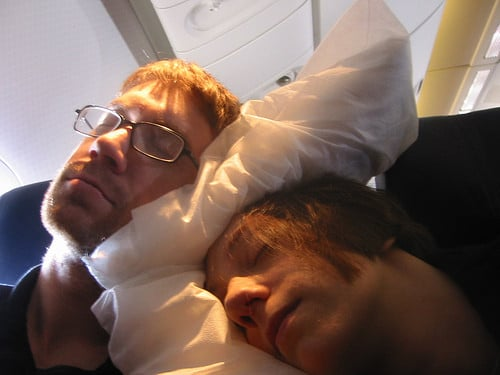 two people sleeping on a plane