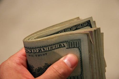 holding 100 dollar bills