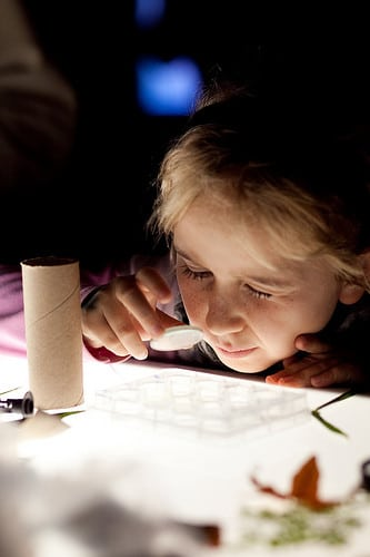 girl looking through microscope